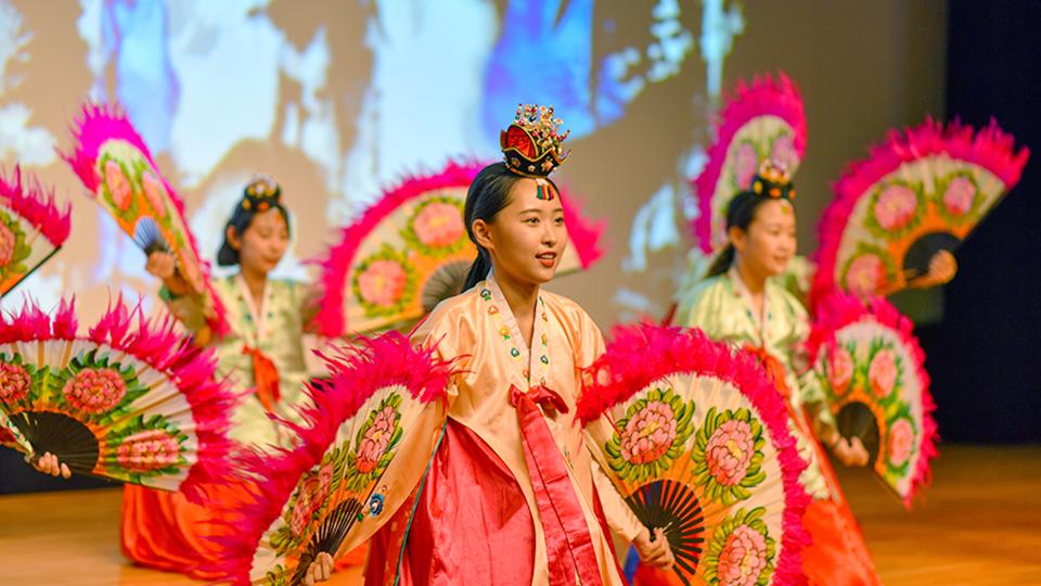 여성봉사단원들이 한복을 입고 족두리를 쓰고 양손에는 꽃이 그려져 있는 부채 가지고 부채춤 공연하는 모습