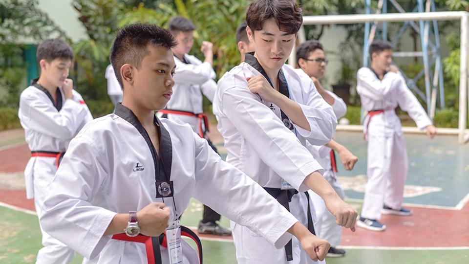 외국 현지 학생들이게 봉사단원이 도복을 입고 태권도를 가르치는 모습