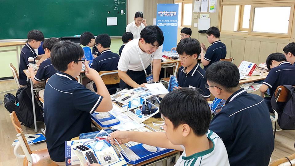 포스코건설 해피빌더-건축교육아카데미 봉사단원들이 한 학급에서 학생들과 교육키트를 활용하여 만드는 모습