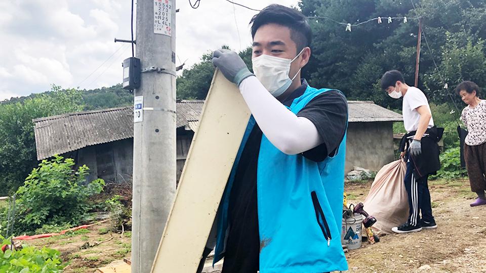 포스코건설 해피빌더- 봉사단원이 마스크를 쓰고 물건을 나르는 모습