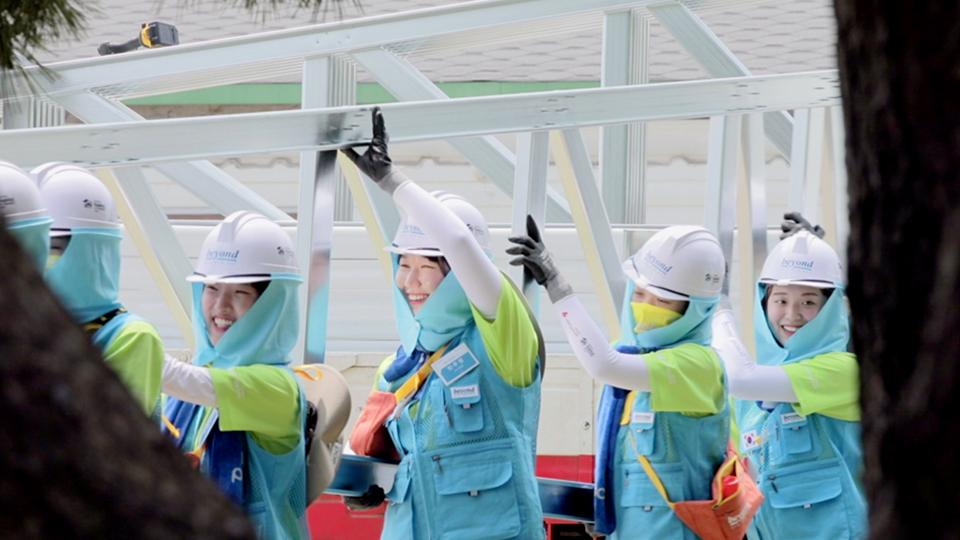 비욘드 봉사단원들이 협력해서 골조물을 즐겁네 나르는 모습