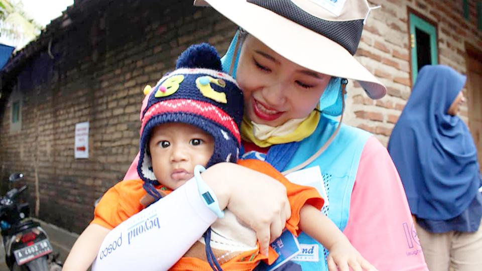 귀여운 모자를 쓴 현지 어린이를 봉사단원이 안고 있는 모습