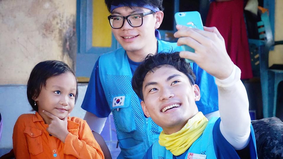 봉사단원과 현지 아이가 즐겁게 핸드폰으로 사진을 찍고 있다.