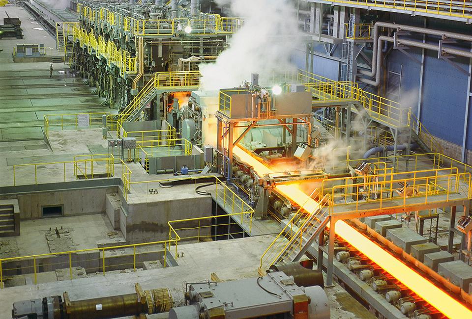 공장 내부에 붉은 황금빛의 철물이 통로를 따라 연기를 내며 흘러가는 모습