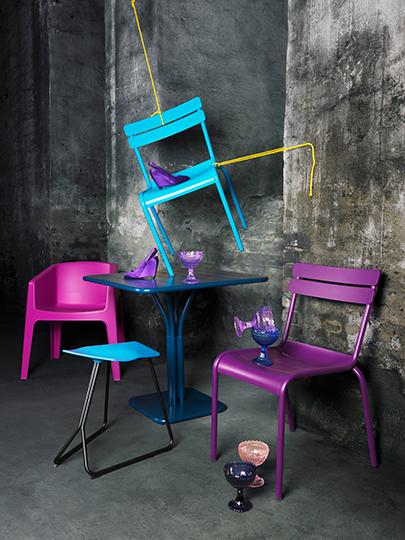 회색 공간에 핫핑크의자  노란색 줄에 하늘색의자가 공중에 달려있고 보라색의자 딥블루색상의 철제 테이블이 있다