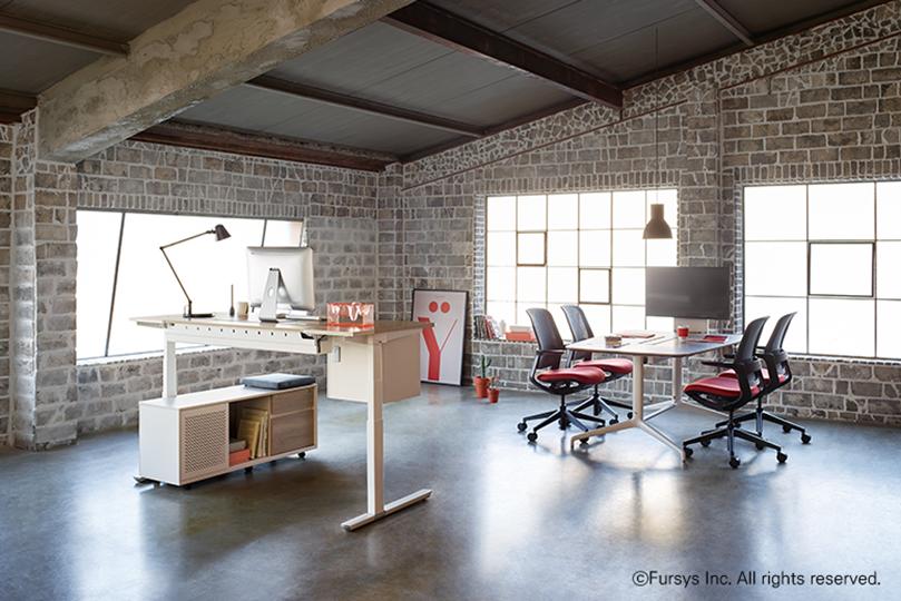벽면에 벽돌로 되어있고 키가 높은 아이보리색 책상과 보통 높이의 책상있는 실내 전경