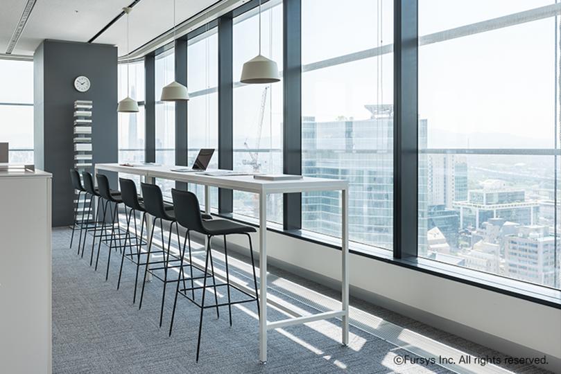 창가앞으로 흰색 높은 긴테이블에 검정색 높은 의자가 있는 사무실 풍경