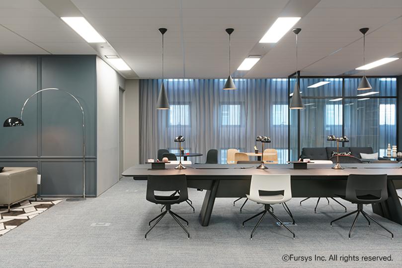 그레이톤으로 이루어진 사무실에 검정색과 희색 의자와 검정색 큰 테이블 아래로 회색 카펫이 깔려있다
