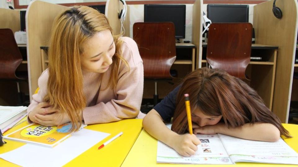 봉사단원이 학생에게 공부를 가르치는 모습
