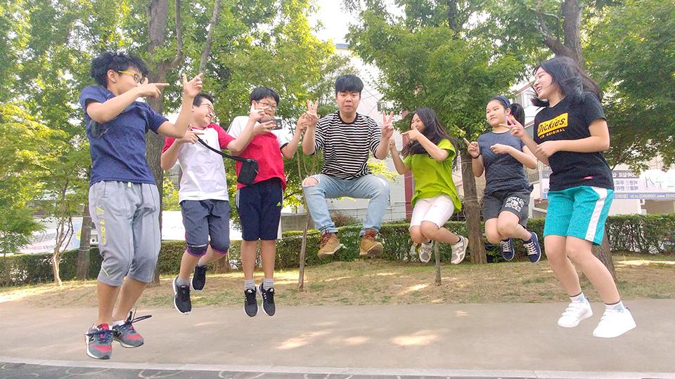봉사단원과 아이들이 공원에서 높게 점프하는 순간을 찍은 사진