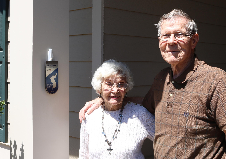 한국전쟁참전용사협회 애틀란타 지회 회계를 담당하고 있는 어반 럼프(Urban Rump)씨와 그의 부인 캐롤 럼프(Carol Rump)씨가 현관에 걸어놓은 기념패 앞에서 사진을 촬영하고 있다.