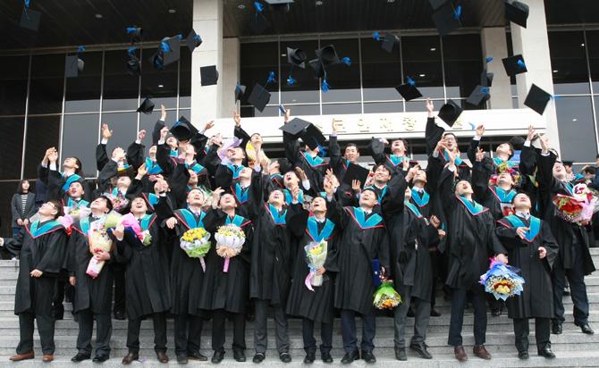 포스코기술대학 1기 졸업식 사진. 졸업생들이 학사모를 높이 던지고 있다.
