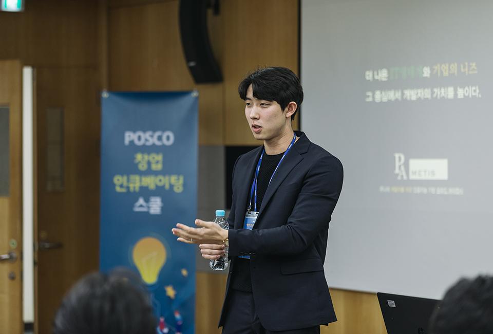 "POSCO 창업 인큐베이팅 스쿨 교육생 한 명이 ""더 나은 IT생태계와 기업의 니즈, 그 중심에서 개발자의 가치를 높이다""가 표출된 스크린 앞에서 발표하는 모습"