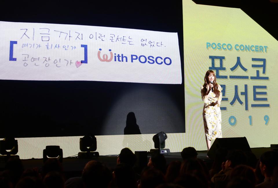 """포스코콘서트 'Hope_Full' 무대에서 MC가 With POSCO 앞의 빈칸 채우기 이벤트를 진행하고 있다. 스크린에는 """"지금까지 이런 콘서트는 없었다. 여기가 회사인가 공연장인가""""라는 재치있는 문구가 나타나 있다."""