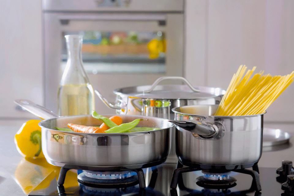 주방 가스레인지 위 파스타와 야채를 담은 스테인리스 냄비들
