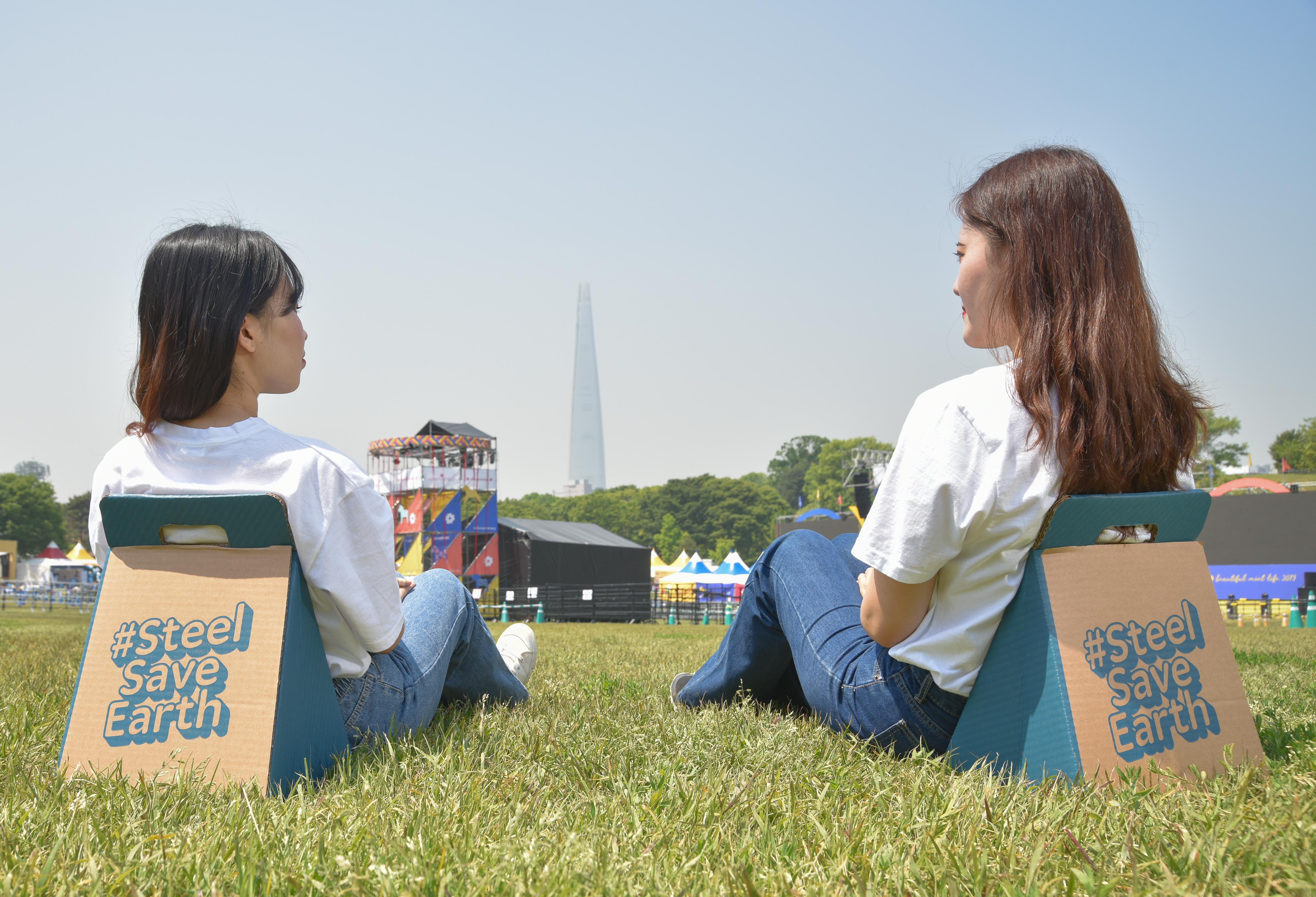 올림픽공원 '뷰티불 민트 라이프' 축제 부스들을 배경으로 #Steel Save Earth가 적힌 간이의자에 앉아 있는 사람들