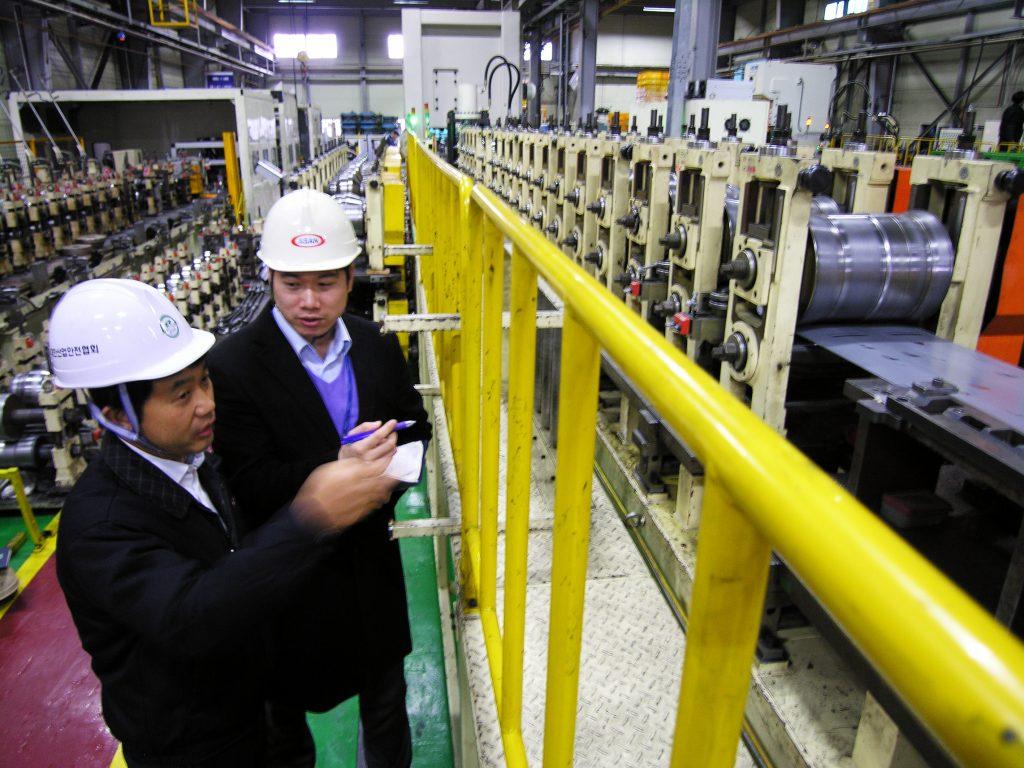 포스코 자동차소재마케팅실 하승호 과장(오른쪽)과 아산 김근호 부장이 롤 포밍 설비에서 포스코 WTP로 생산하는 차 부품의 품질에 대해 얘기를 나누고 있다.