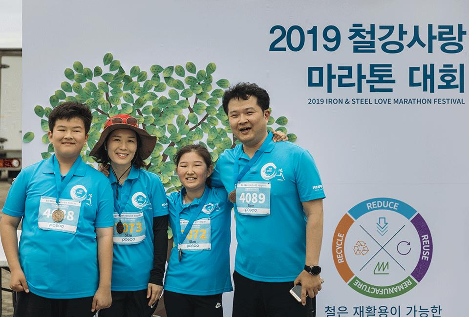 2019 철강사랑 마라톤 대회 대형 입간판 앞에서 사진을 찍는 이정민 차장과 가족들