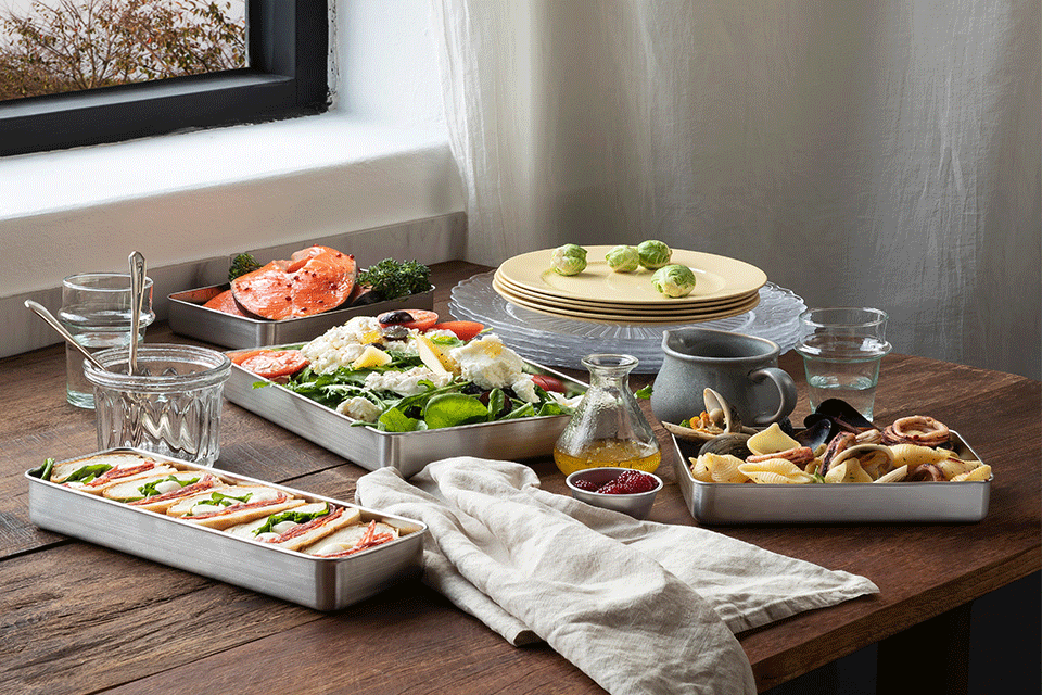 4종의 직사각형 용기로 이루어진 스텐킵스 시스템에 샌드위치 샐러드등 음식들이 예쁘게 담겨있다.
