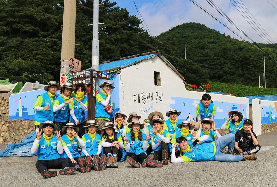 대동배2리 마을 담벼락 앞에서 기념촬영을 하는 비욘더들