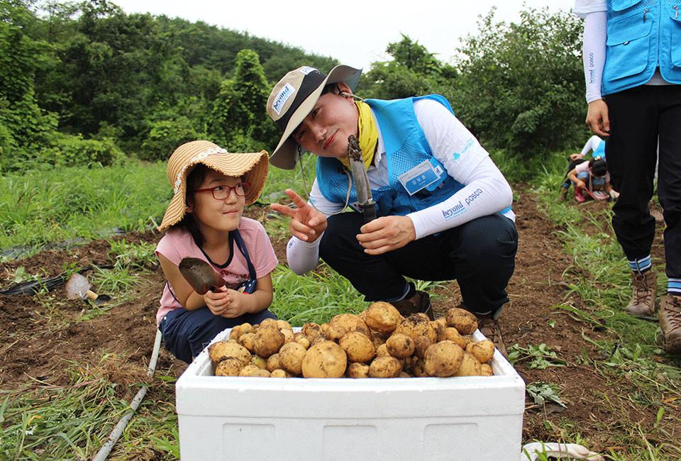 아이와 함께 감자를 수확해 기념촬영을 하고 있는 비욘더
