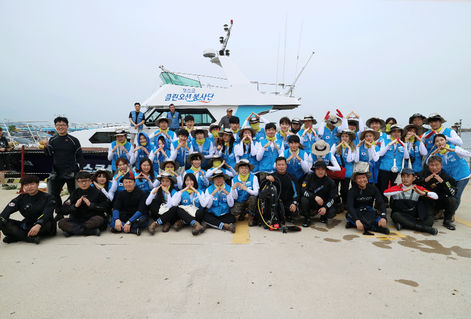 배 앞에서 기념촬영을 하고 있는 비욘더들과 포스코 재능봉사단원들