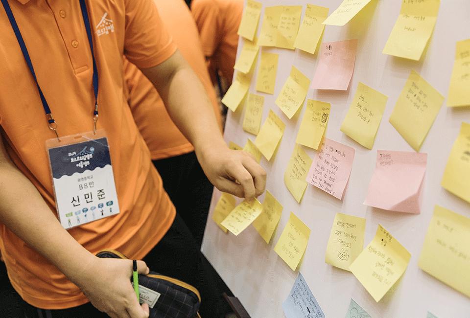 포스트잇에 질문을 작성해 붙이는 청소년