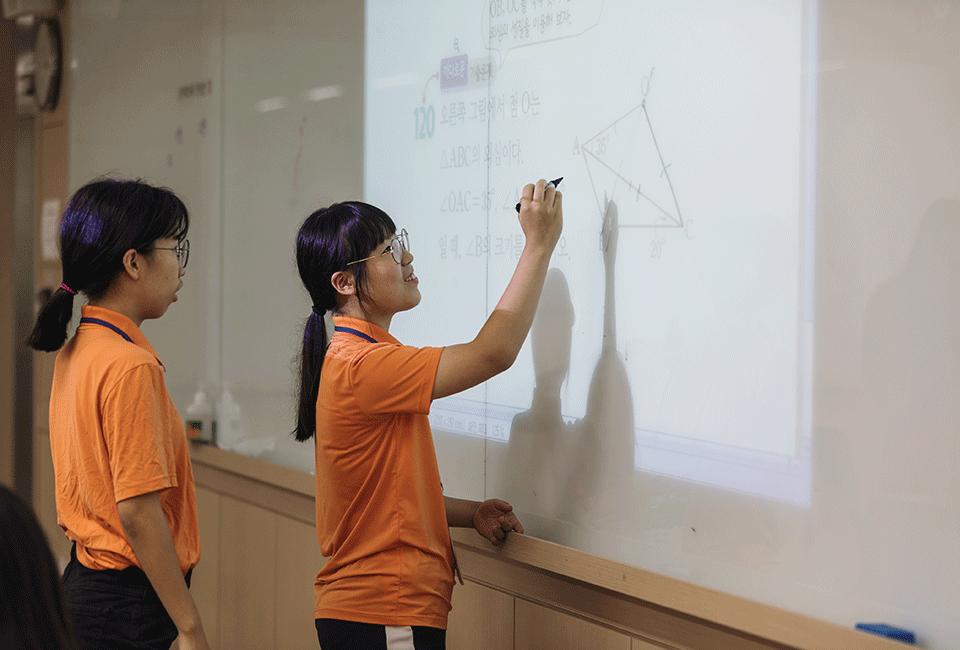 칠판에 수학 문제를 풀고 있는 청소년들