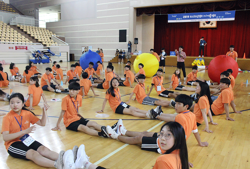 큰공굴리기 게임을 하기 위해 다리를 맞대고 앉아있는 청소년들