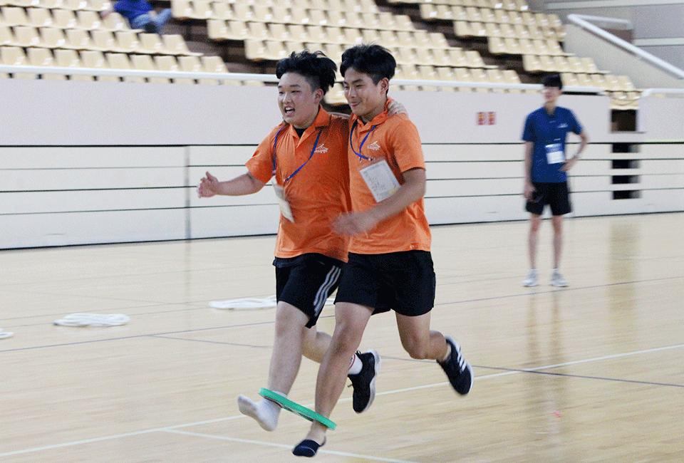 서로 한 발씩 묶고 달리기를 하는 청소년들
