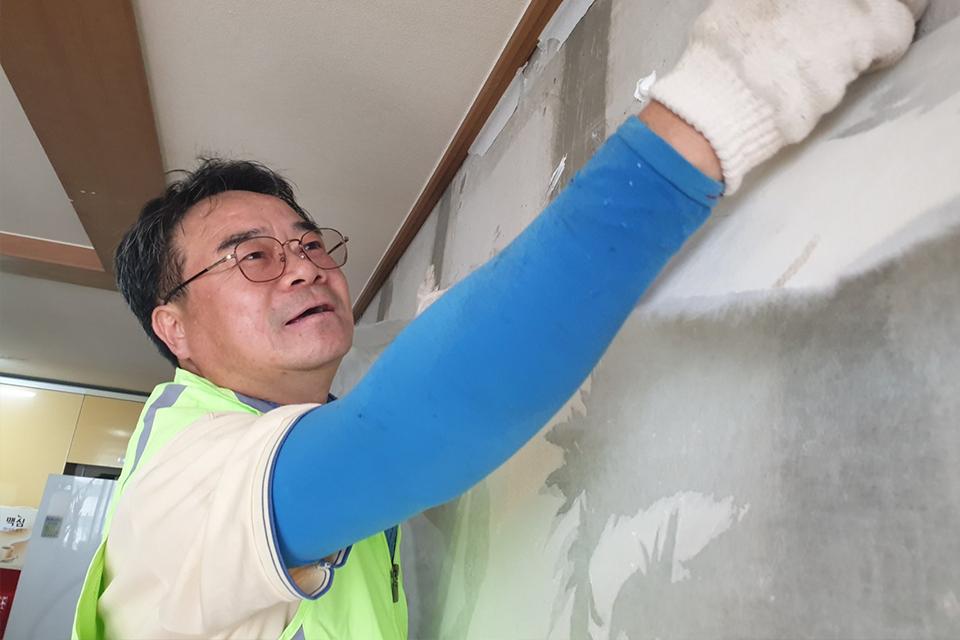 광양 제선부 원료공장 최광석 과장이 도배 자원봉사를 하고있다.