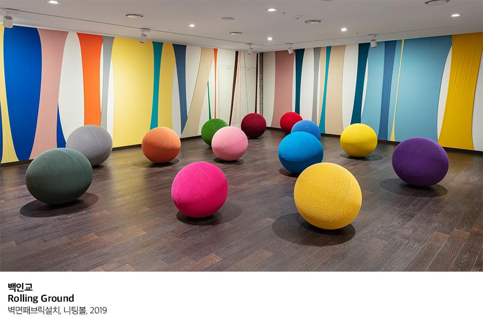 백인교 Rolling Ground 벽면패브릭설치, 니팅볼, 2019 벽면에는 여러 색이 보이며 바닥에는 여러 색의 벽면을 말아 놓은 듯 한 형상의 원형 물체들이 보인다. 알록달록한 니팅볼들을 이리저리 튕기거나 굴려 온 가족이 함께 공놀이를 할 수 있다.