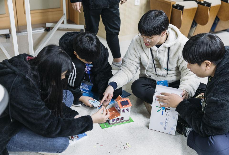학생들이 머리를 맞대고 이리저리 맞춰보고 휴대폰을 연결해 작동시켜 보고있다.