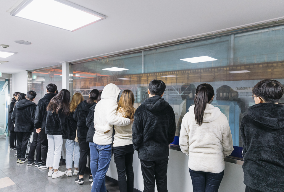 옹기종기 모여 창 넘어 작업현장을 보고 있는 학생들