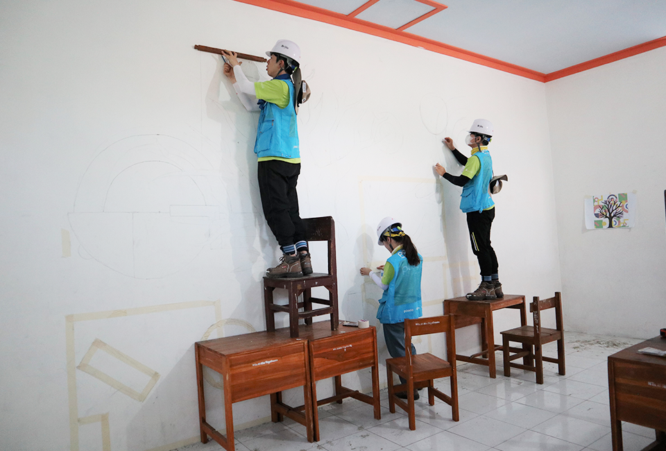 교실 벽에 그림을 그리고 있다 높은 곳은 의자와 책상에 올라가 그림을 그리며 교실 안을 꾸며주고 있다.