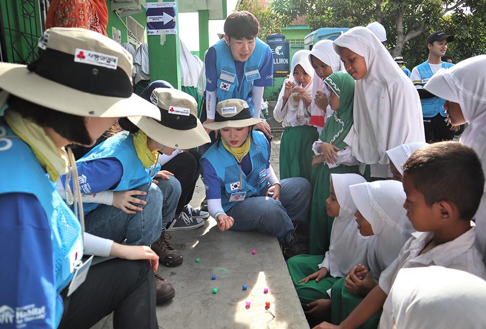 쉬는시간 봉사단과 수혜학교학생들이 공기놀이를 하고있다