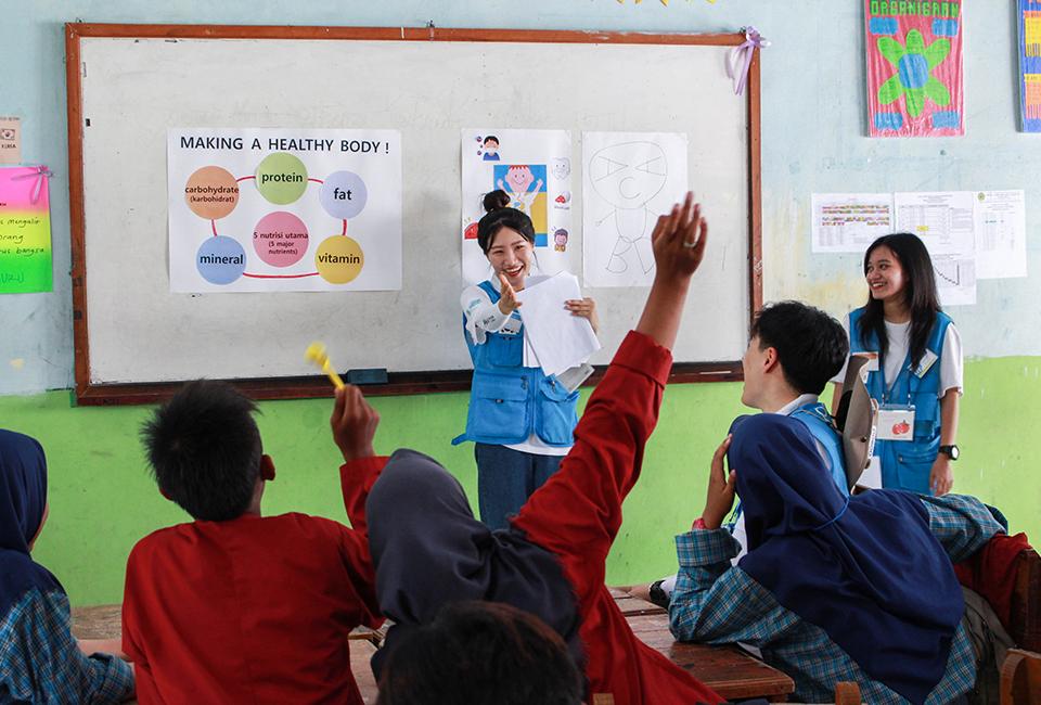 즐거운 분위기 속에 교육봉사 하는 모습 수혜학교 학생들은 손을 들며 발표를 한다