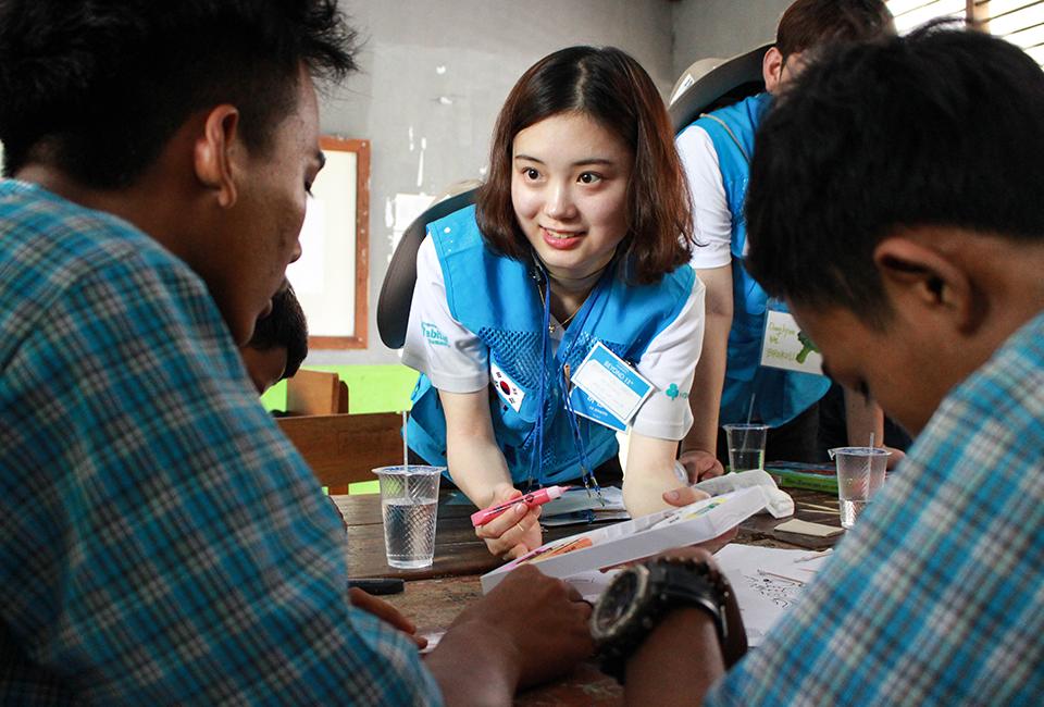 봉사단원이 교육봉사 시간 수혜학교 학생들에게 친절하게 설명하고 있다
