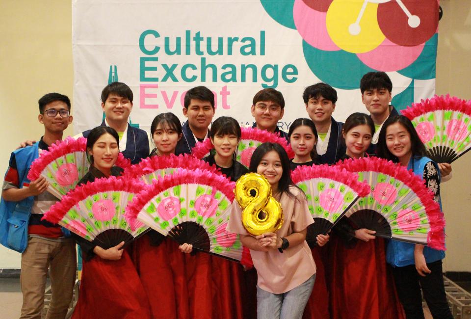 부채 춤 공연이 끝난 후 조원들과 Cultural Exchange Event 현수막 앞에서 단체사진을 찍고있다