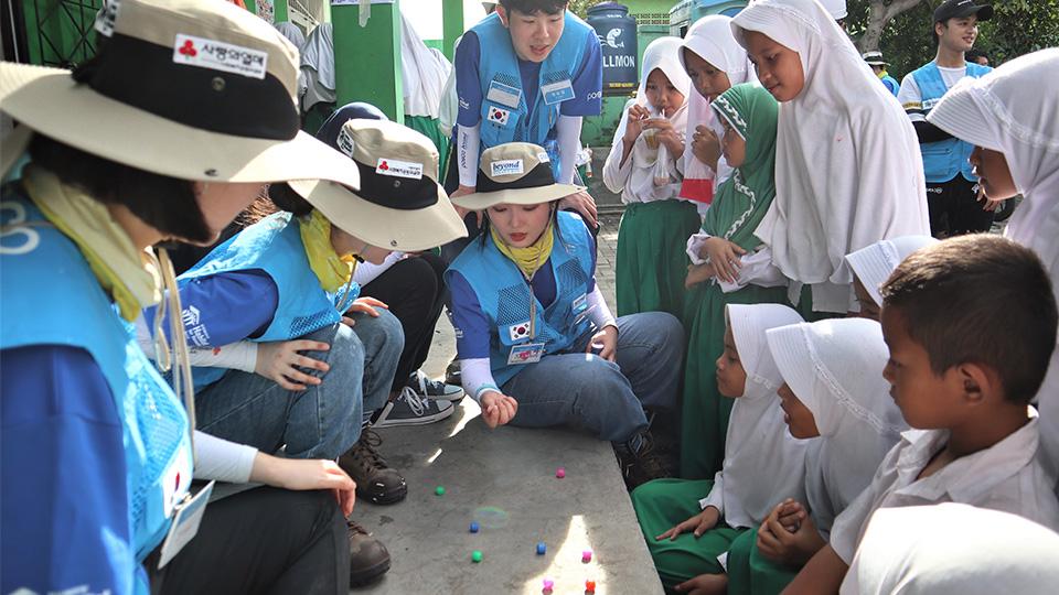 비욘드 봉사단원들이 수혜 학교 학생들과 휴게시간에 공기놀이를 하고 있다