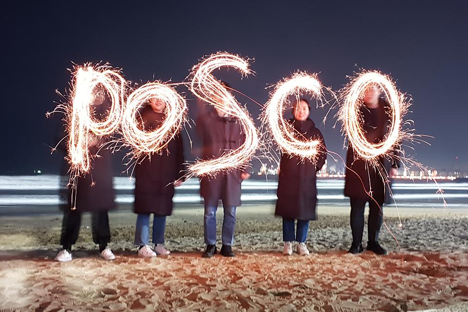 신입사원들이 해변가에서 불꽃을 갖고 POSCO를 그리고 있다.