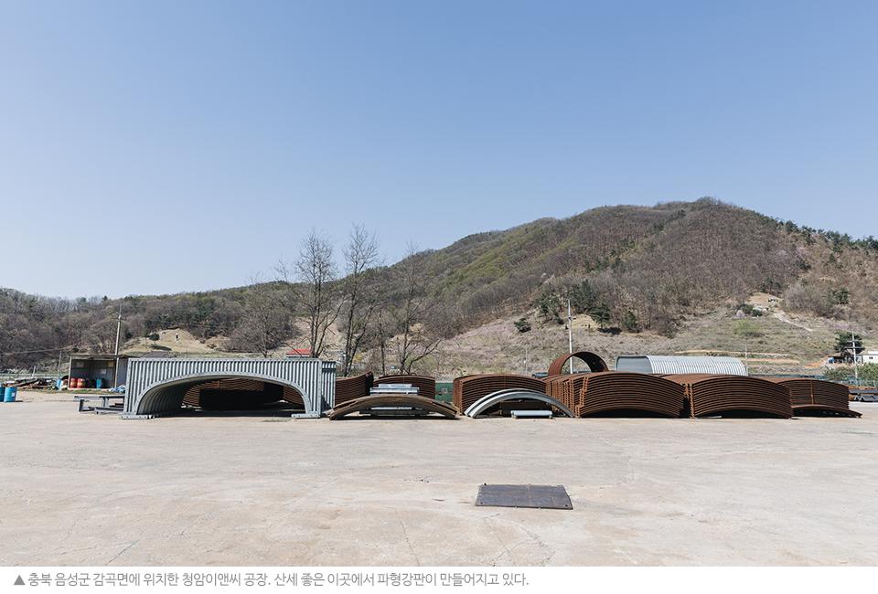 충북 음성군 감곡면에 위치한 청암이앤씨 공장. 산세 좋은 이 곳에서 파형강판이 만들어지고 있다. 쌓아 놓은 철재 뒤로 산자락이 펼쳐져 있다.
