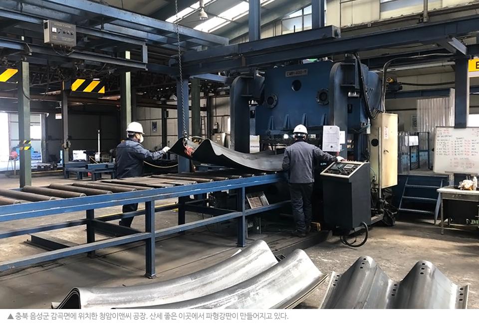 청암이앤씨 공장 내부. 노동자 두 명이 롤러컨베이어 위에 파형강판을 두고 작업하고 있다.