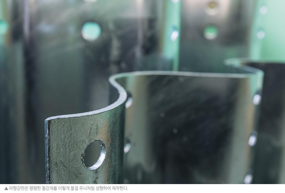 파형강판은 평평한 철강재를 물결 무늬처럼 성형하여 제작한다. 곡선 모양의 파형강판 사진.