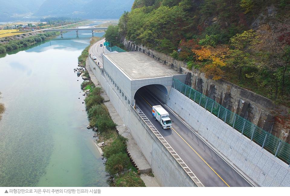 파형강판으로 지은 우리 주변의 다양한 인프라 시설들. 왼쪽으로 강이 있 오른쪽엔 터널이 있는 2차선 도로가 보인다.